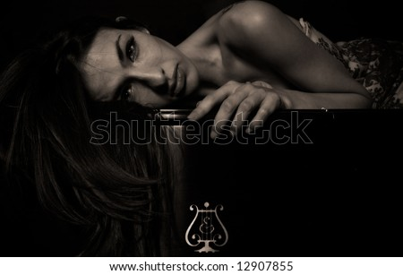 Young female model in a piano store. - stock photo