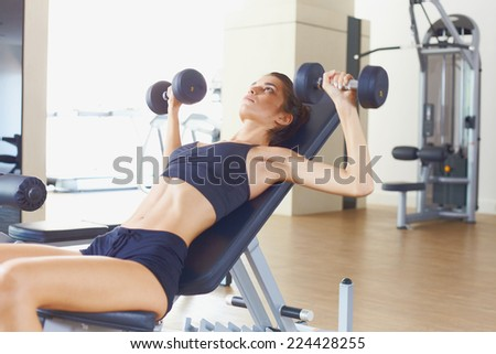 Young female model in fitness gym doing exercisec