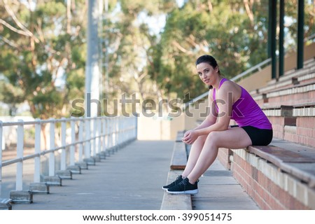 Young female model in sportswear sat on the bences of an empty sports stadium - stock photo