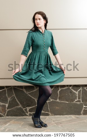 Young female model posing outdoor while pulling her green dress up - stock photo
