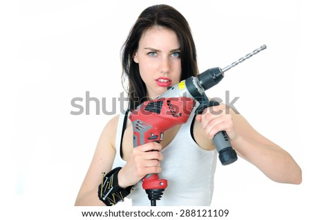 Young female model wearing white top and jeans' shorts. Girl holding big driller, keeping key, screwdriver and small hammer in her pocket.