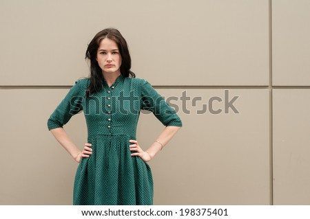 Young female model with hands on her hips and looking at the camera in front of a metal wall. She is wearing a green summer dress with white dots. - stock photo