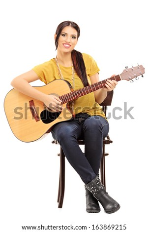 Young female musician seated on a wooden chair holding an acoustic guitar isolated on white background