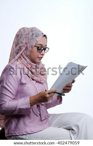 Young female muslim lady wearing hijab and spectacle reading with white background