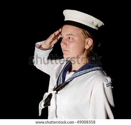 young female navy seaman saluting on black - stock photo