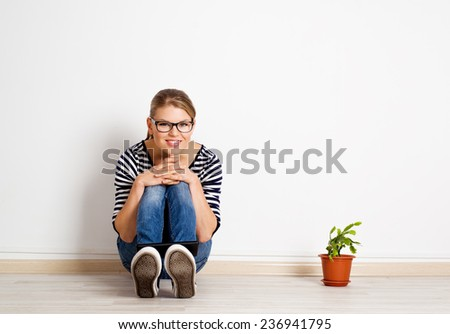 Young female new realty owner.  Pretty smiling woman sitting on the floor of new empty room. Mortgage and loan concept. - stock photo