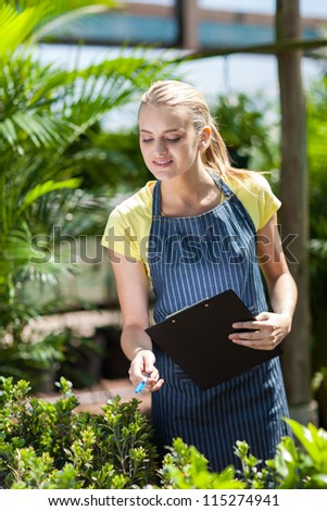 young female nursery worker counting stock in greenhouse - stock photo