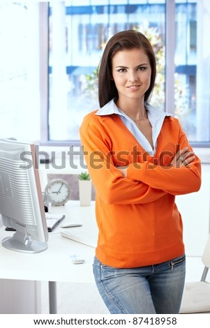 Young female office worker smiling arms crossed in bright office.? - stock photo