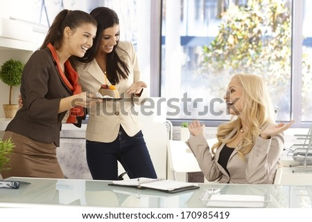 Young female office workers celebrating ones birthday, bringing cake with candle. - stock photo