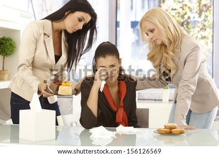 Young female office workers comforting crying colleague by cakes and doughnut. - stock photo