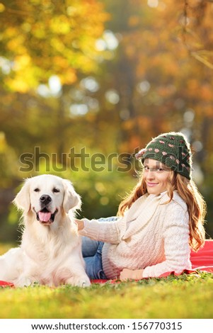 Young female on a grass with her dog in autumn - stock photo