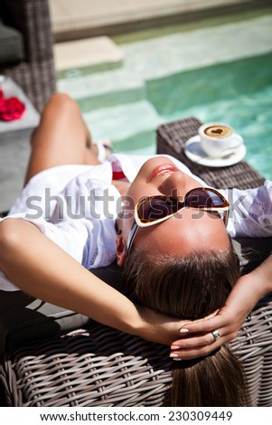 Young female on a vacation, sunbathing with morning coffee on a modern recliner next to a modern-style pool - stock photo