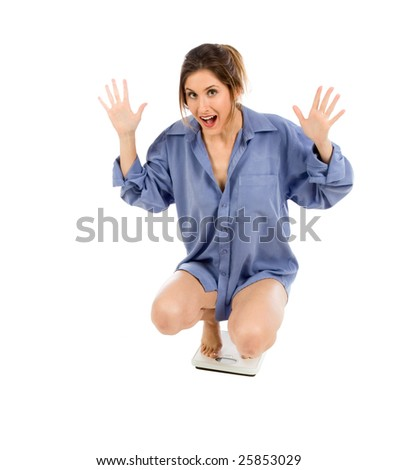 Young female on bathroom weight scales, checking weight and extremely thrilled and excited by results she achieve form her diet - stock photo