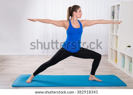 Young Female On Exercise Mat Doing Exercise At Home