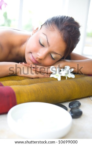Young female on massage bed with aromatherapy bowl and therapy pebbles.