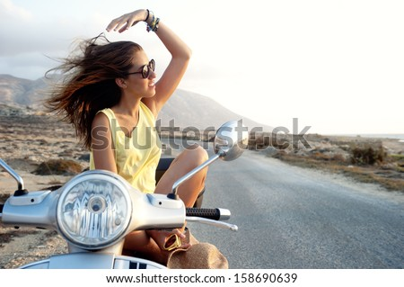 Young female on motorcycle trip. Young female enjoys a motorcycle trip and admires the view - stock photo
