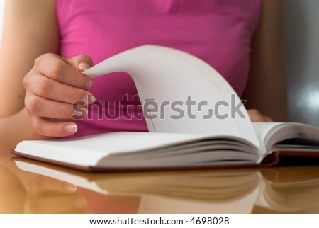 Young female opens notebook and planning her schedule. - stock photo