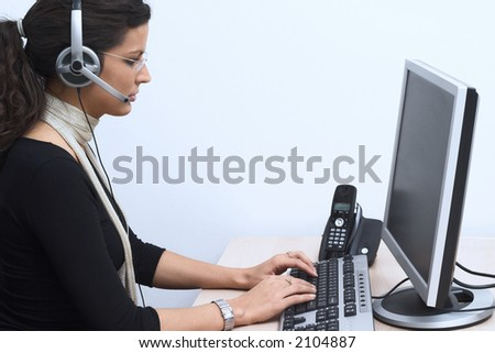 Young female operator wearing a headset works on a desktop computer. - stock photo