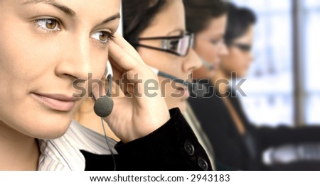Young female operators in headset. - stock photo