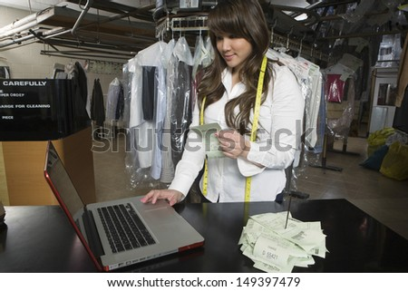 Young female owner calculating amounts on laptop at counter in laundry - stock photo