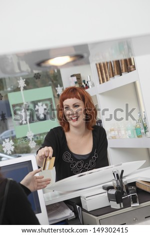 Young female owner taking payment in hairdressing salon - stock photo
