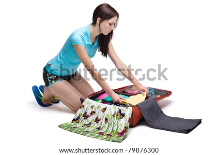 Young Female packing suitcase isolated on white - stock photo