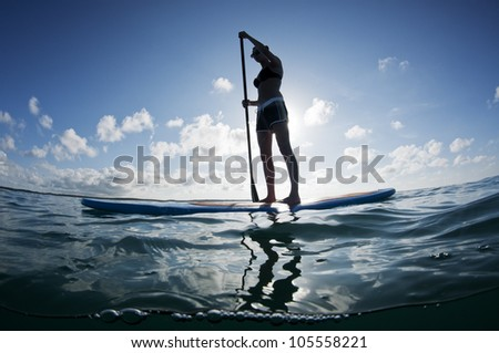 young female paddles a paddleboard off a Bahamian island - stock photo