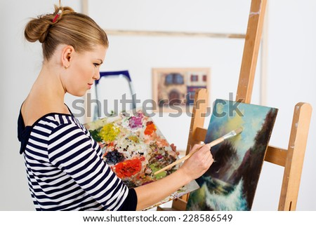 Young female paint artist working with paintbrush over picture. Attractive woman painter standing at easel with color palette.  - stock photo