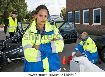Young female paramedic posing confidently in front of a car accident site - stock photo