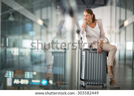 Young female passenger at the airport, about to check-in (color toned image; shallow DOF) - stock photo