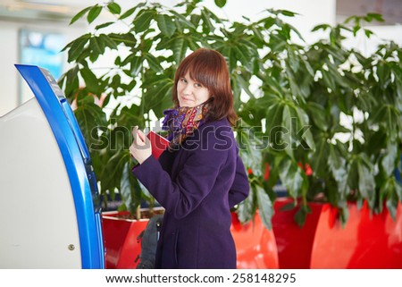 Young female passenger at the airport, doing self check-in - stock photo
