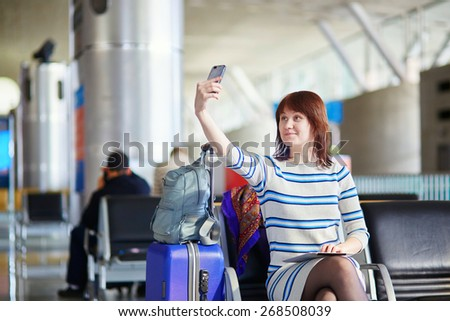 Young female passenger at the airport, making selfie with her mobile phone - stock photo
