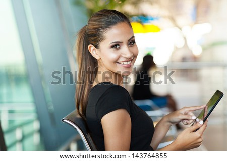 young female passenger at the airport using her tablet computer while waiting for flight - stock photo