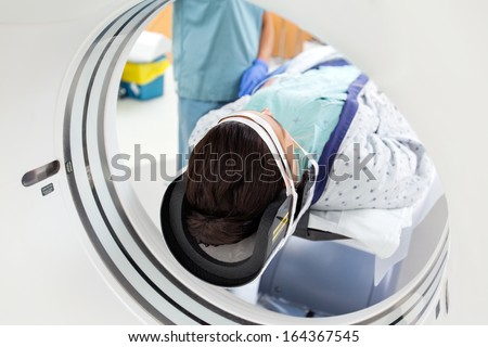 Young female patient undergoing CT scan test in examination room - stock photo