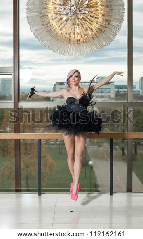 Young female performing in pink high heels and feather dress - stock photo
