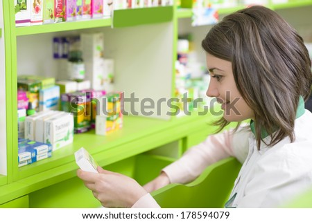 Young female pharmacist in a drugstore reading a recipe - stock photo