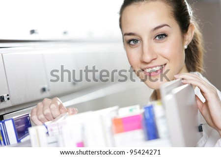 Young female pharmacist reaching for medicine