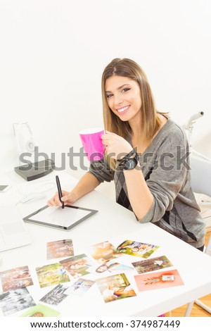Young female photographer at home office sitting, smiling, retouching photos on digital tablet, drinking coffee. Modern freelance blonde girl working from home. Vertical, medium retouch, no filter.