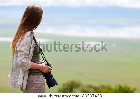 Young female photographer enjoying views of Ngorongoro crater in Tanzania - stock photo