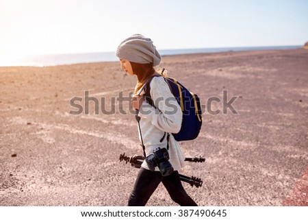 Young female photographer in sweater and hat walking with camera, backpack and tripod on the deserted landscape backround