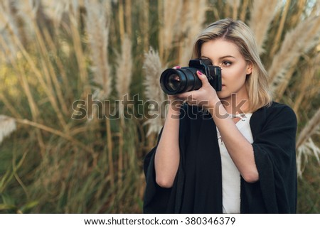 Young female photographer outdoors with digital camera and zoom lens - stock photo