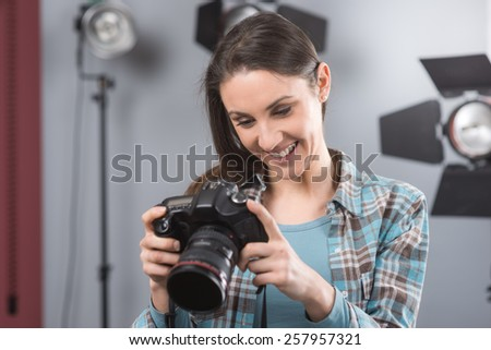 Young female photographer posing in her professional studio, holding a digital camera with lighting equipment on background - stock photo
