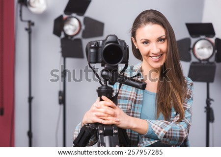 Young female photographer posing in her studio with a digital camera on a tripod and lighting equipment on the background - stock photo