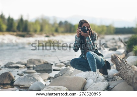 Young female photographer shooting, natural landscape on background - stock photo