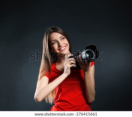 Young female photographer taking photos on black background - stock photo