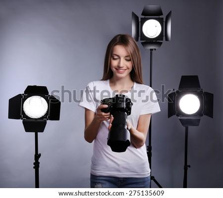 Young female photographer taking photos on grey background - stock photo