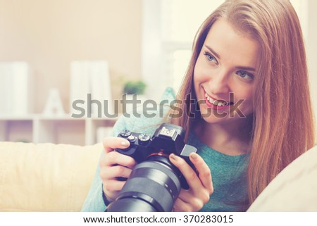 Young female photographer using a DSLR camera  - stock photo