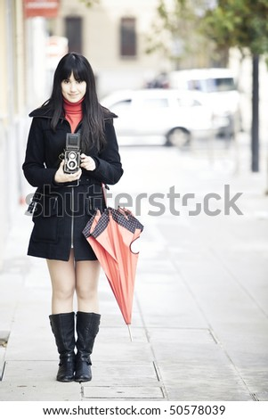 Young female photographer using old 6x6 camera. - stock photo
