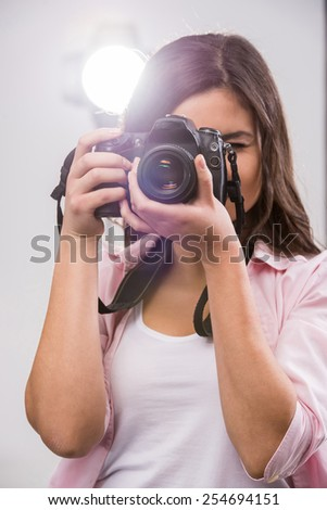 Young female photographer with camera in professionally equipped studio. - stock photo
