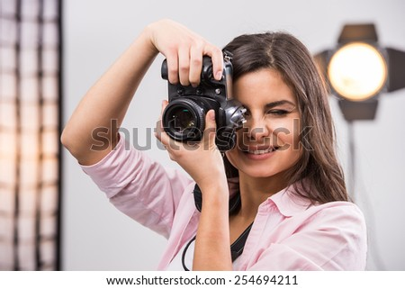 Young female photographer with camera in professionally equipped studio.